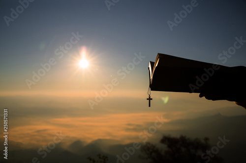 Silhouette of human hand holding bible and cross, the background is the sunrise Billede på lærred