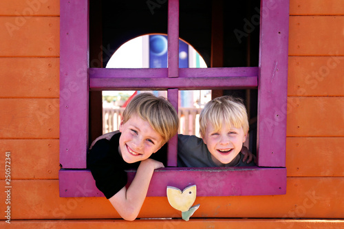 Tablou Canvas Happy Little Kids Smiling at the Park as they Peek out the Window of a Clubhouse