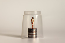 A Glass Ceiling Concept. Miniature Women And Coins.