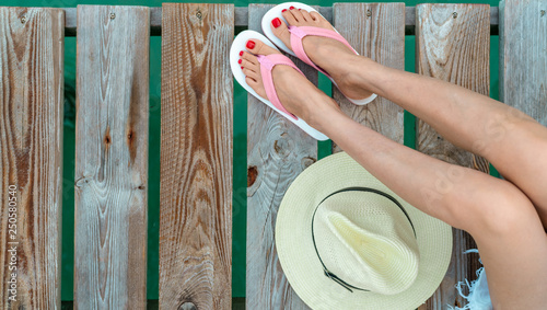 Poster Pedicure Young Asian woman with red pedicure wearing pink and white sandals sit on wooden bridge and put hat beside legs on holiday. Summer vacation. Summer vibes. Woman travel alone. Happy backpacker girl.