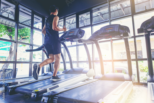 Canvas Print Fit man running in machine treadmill at fitness gym