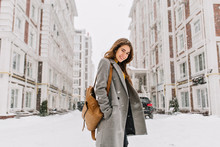 Stylish Lady With Brown Backpack Walking Around City Under Snowfall. Outdoor Photo Of Pretty Girl With Charming Smile Posing In Gray Coat On Urban Background In Winter Day.
