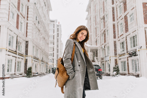 Carta da parati Stylish lady with brown backpack walking around city under snowfall