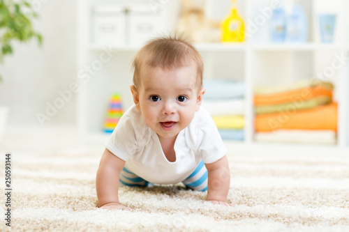 Nursery baby boy crawling on floor indoors at home Canvas Print