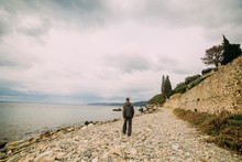 A Man Walks The Stony Shore Of...