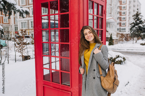 Obraz Stylish british portrait of charming young woman with long brunette hair walking on street near red telephone box on street full with snow. Cold snow weather, smiling, winter holidays, joy - fototapety do salonu