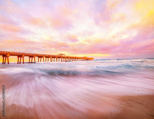 Wall Murals Light pink Pier at sunset on the coast of the Atlantic Ocean. Florida. USA. Long exposure.