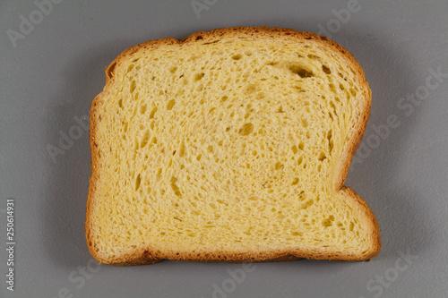 Fotografie, Obraz  One slice of brioche on gray background