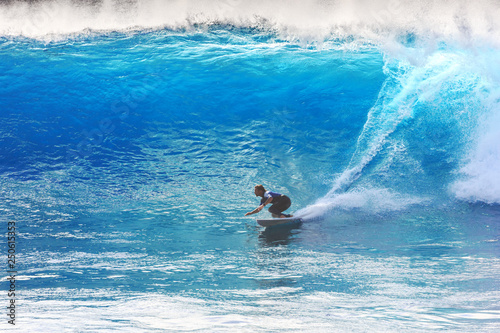 Photo Silhouette surfer riding the big blue surf waves on the island Madeira, Portugal