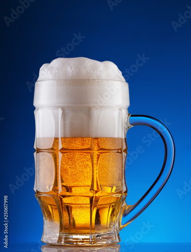 Photo  Faceted mug of light beer with foam on blue background