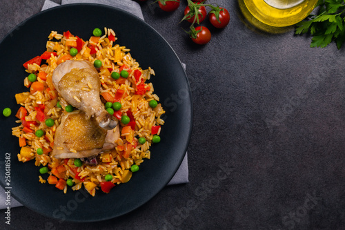 Obraz Arroz con pollo. Baked pieces of chicken with bone, rice with paprika and peas. - fototapety do salonu