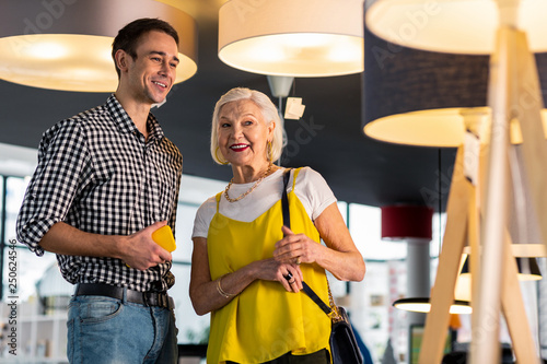 Fotografie, Obraz  Beaming gorgeous senior lady discussing lamps buying with younger beau
