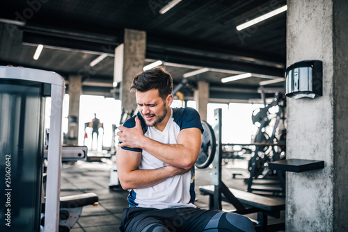 Obraz Portrait of a handsome man with strong facial expresion and injured arm while exercising in the gym. - fototapety do salonu