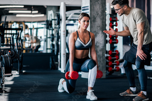 Fototapeta Young muscular woman doing weighted lunge with dumbbells, with personal trainer motivating her
