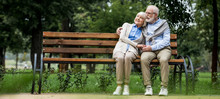 Happy Senior Couple Hugging While Sitting On Wooden Bench In Park