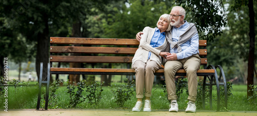 happy senior couple hugging while sitting on wooden bench in park Canvas Print