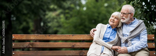 Fotomural smiling senior couple embracing while sitting on wooden bench in park