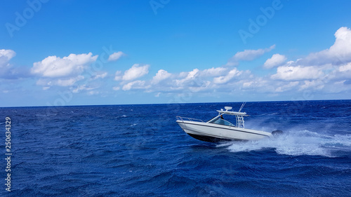 Fotografija Speed fishing tender boat jumping the waves in the sea and cruising the blue ocean day in Bahamas