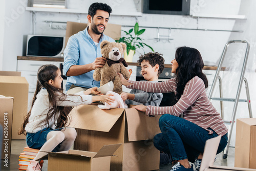 Valokuva  cheerful latin father holding soft toy near hispanic family while unpacking boxe