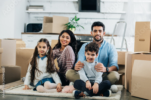 Photo  happy latin husband and wife sitting in carpet with cute children in new home