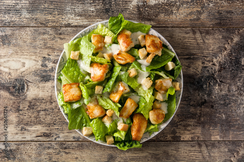 Fotografía  Caesar salad with lettuce,chicken and croutons on wooden table.