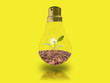 Leinwanddruck Bild - A small tree in a light bulb on a yellow background with energy-saving concepts to protect the environment.