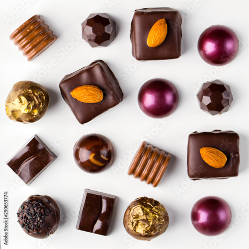 Different homemade chocolate candys on the white background, top view, close up, nobody