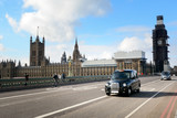 Fototapeta Londyn - Black cabs drive on the London street with illuminated taxi sign