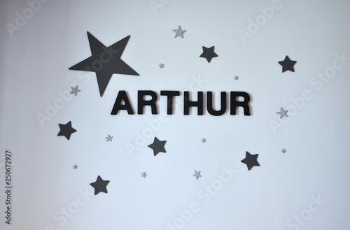 Photo Prénom Arthur écrit sur un mur entouré d'étoiles