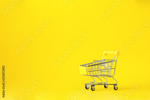 Fotografía  Shopping cart trolley basket is empty on a bright yellow background