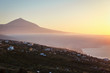 Sunset with the silhouette of volcano Teide in the background, above the clouds, below the clouds the city of Santa Cruz, Tenerife island, Spain