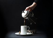 Woman's Hand Pouring Coffee In...