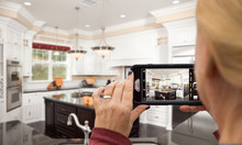 Woman Taking Pictures Of A Custom Kitchen With Her Smart Phone