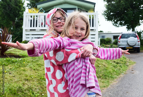 Fotografie, Tablou  Two sisters playing outside there static holiday home cuddling and playing