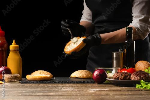 Slika na platnu The chef prepares the sauce for the burger and puts on a fresh hamburger bun