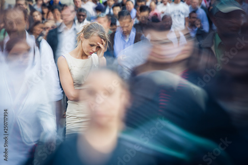 Fotografie, Obraz  Depressed young woman feeling alone amid a crowd of people in a big city