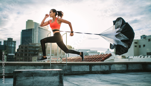 Fotografie, Obraz  Woman running on rooftop with a resistance parachute