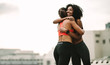 canvas print picture - Smiling athlete giving a hug to her friend during workout