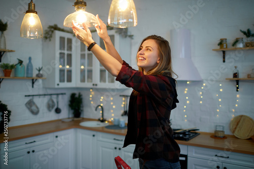 Photo  Young happy woman twists a light bulb in the kitchen lamp