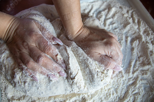 Woman's hands with manicured nails work with dough in the kitchen Canvas Print