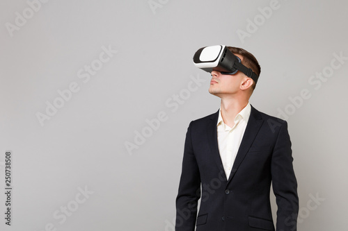 Photo  Portrait of young business man in classic black suit and white shirt looking up in headset isolated on grey wall background in studio
