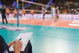notebook of volleyball coach with the match in the background