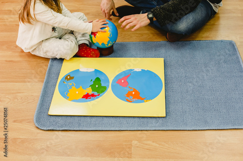 Fotografía  Girl with her teacher using montessori materials to study the geography of the globe with a map of colors