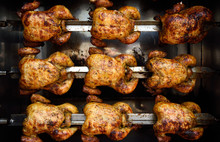 Rows Of Hot Roasted Skewered Whole Rotisserie Chickens, In Colombia, South America