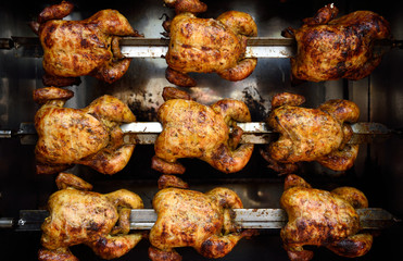 Rows of hot roasted skewered whole rotisserie chickens, in Colombia, South America.