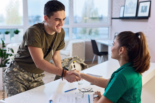 Fotografiet  Happy military man shaking hands with female doctor at clinic.