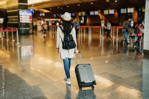 Cuadros en Lienzo  back view of young asian businesswoman in business travel trip drag luggage suitcase walking to lobby