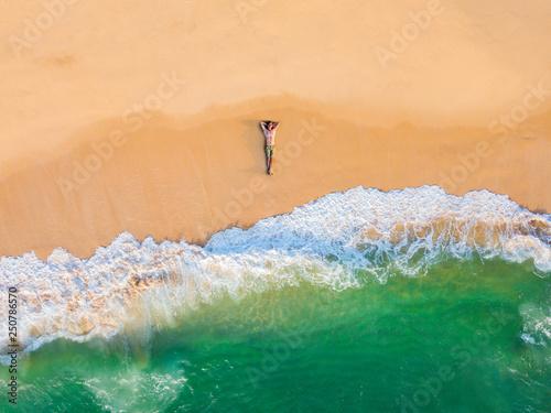 Fotografie, Obraz  The guy lies on a sandy beach on a tropical island. Drone view