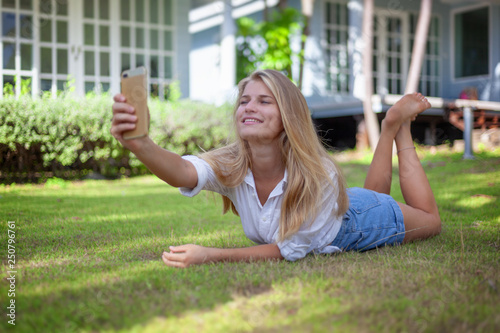 Beautiful blonde girl, on a summer green lawn, with a smartphone in her hands en Canvas-taulu