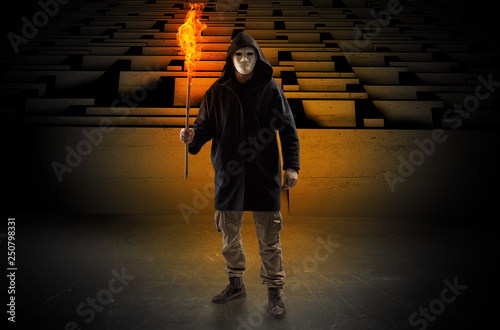 Photo Ugly, aberrant man coming out from the labyrinth with burning flambeau on his ha